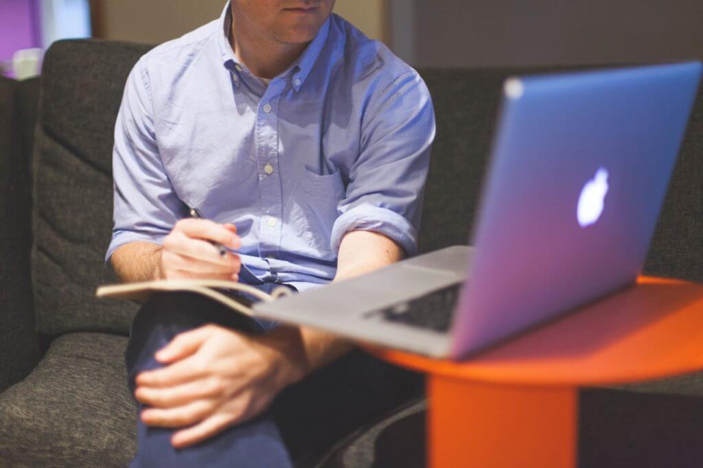 man-notes-macbook-computer
